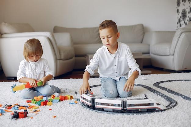 Crianças brincando com trem de lego e brinquedo em uma sala de jogos