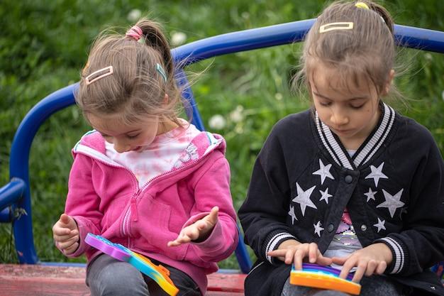 Crianças brincando com um brinquedo popular estalam-no, seguram nas mãos um jogo anti-stress de silicone.