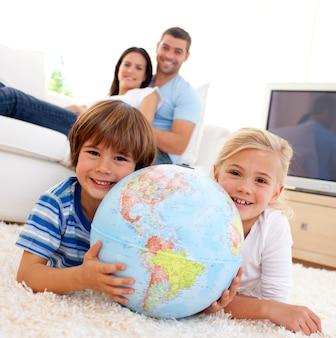 Crianças brincando com um globo terrestre em casa