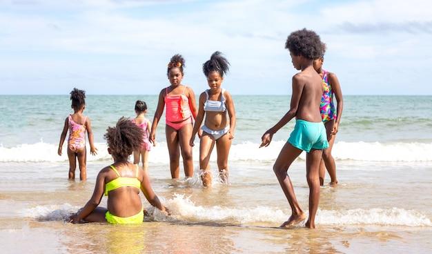 Crianças brincando correndo na areia na praia