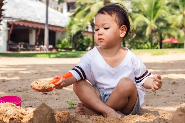 Crianças brincando de areia na praia. momento de felicidade nas férias de verão.