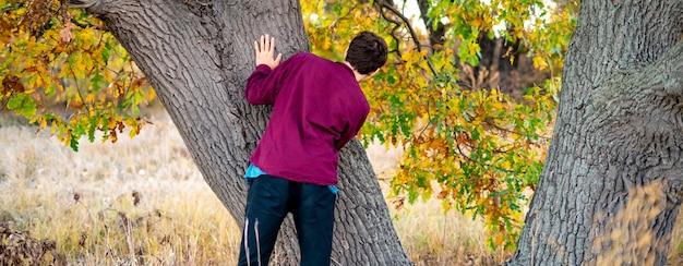 Crianças brincando de esconde-esconde no parque. escondendo atrás da árvore