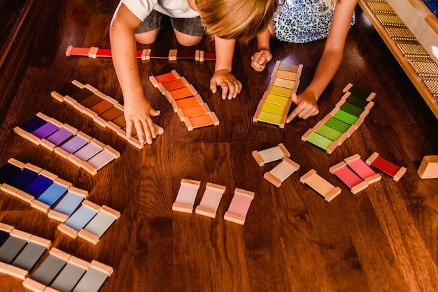 Crianças brincando e aprendendo com tablets cor montessori