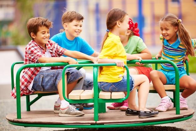 Crianças brincando e rindo com o carrossel