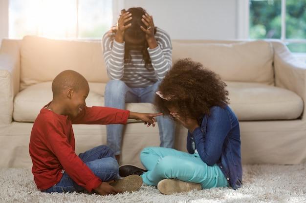 Crianças brincando enquanto mãe sentada deprimida