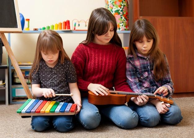 Crianças brincando junto com guitarra e xilofone