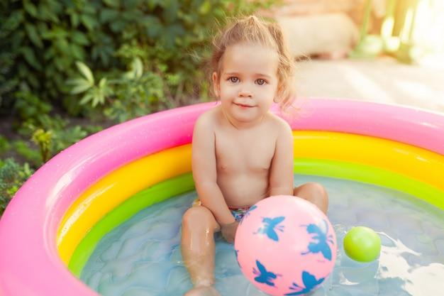Crianças brincando na piscina de bebê inflável.