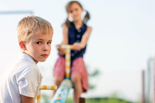 Crianças brincando no balanço. menino em foco e garota turva por trás.