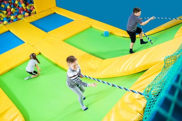 Crianças brincando no centro de trampolim pulando e subindo com corda