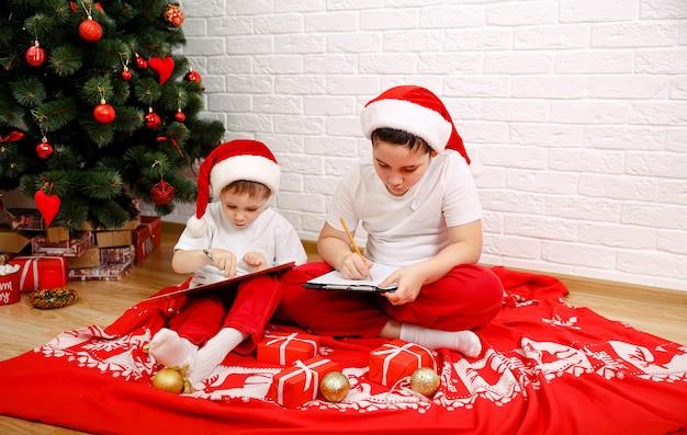 Crianças brincando perto da árvore de natal com presentes na véspera de natal