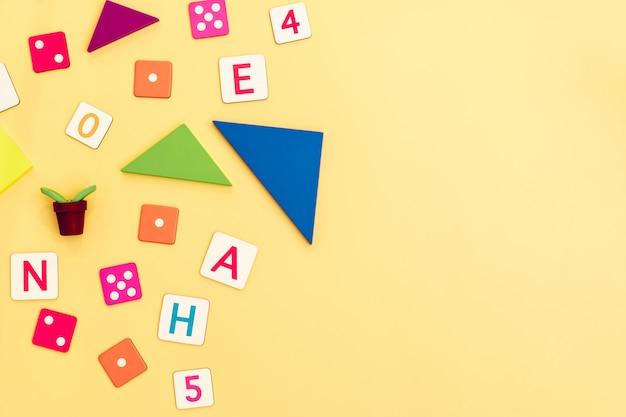 Crianças brinquedos no fundo amarelo com brinquedos plana leigos vista superior com o centro vazio