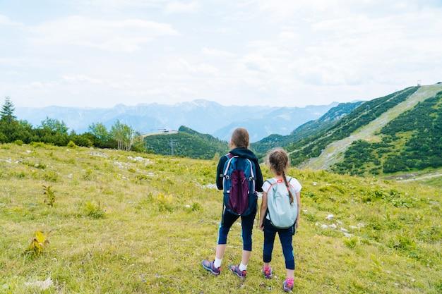 Crianças, caminhadas no lindo dia de verão nas montanhas