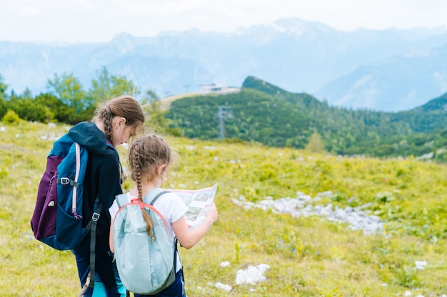 Crianças, caminhadas num lindo dia de verão nas montanhas dos alpes, áustria, descansando na rocha. as crianças olham para os picos das montanhas do mapa no vale.