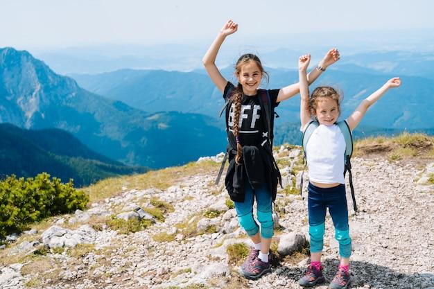 Crianças, caminhadas num lindo dia de verão nas montanhas dos alpes, áustria.
