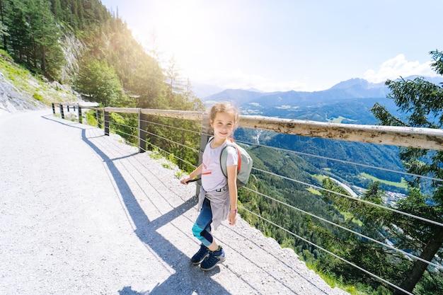 Crianças caminhando em um dia de verão nos alpes, na áustria, descansando na rocha e admirando a vista incrível para os picos das montanhas. férias em família ativas com crianças.
