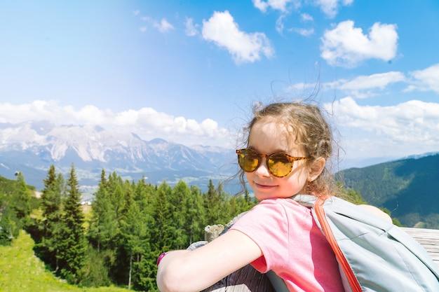 Crianças caminhando em um lindo dia de verão nos alpes, na áustria, descansando na rocha e admirando a vista incrível dos picos das montanhas.
