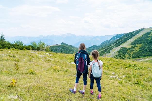Crianças caminhando em um lindo dia de verão nos alpes, na áustria, e admiram a vista incrível para os picos das montanhas.