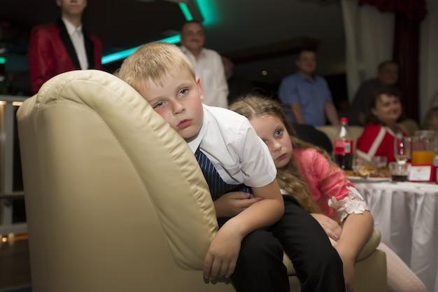 Crianças cansadas caíram no sofá. crianças no casamento. crianças cansadas em uma festa