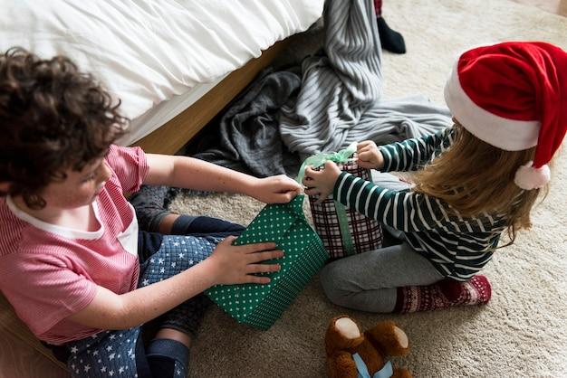 Crianças caucasianas desembrulhando presentes de natal