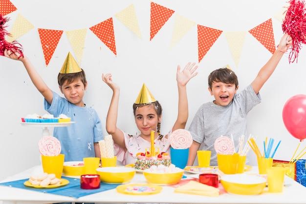 Crianças celebrando festa de aniversário em casa com variedade de comida na mesa