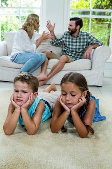 Crianças chateadas mentindo contra pais brigando em casa