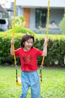 Crianças chinesas brincando de balanço, crianças se divertindo no parquinho, menina feliz