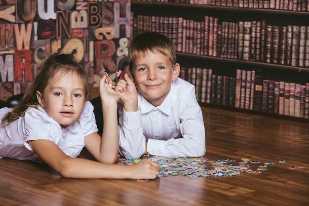 Crianças colecionam o quebra-cabeça colorido na biblioteca