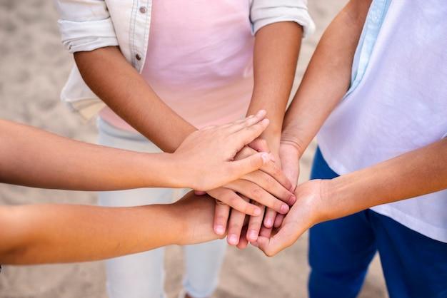 Crianças colocando as mãos uma em cima da outra