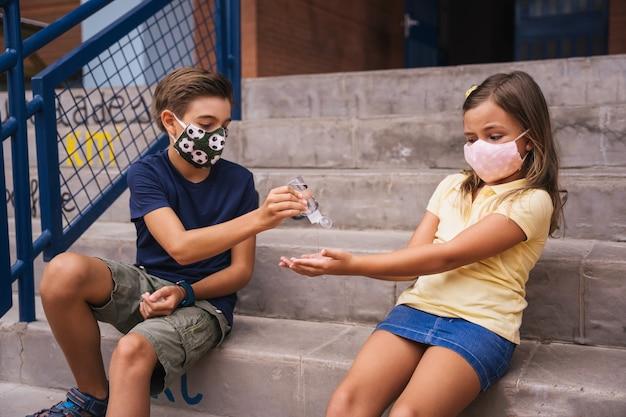 Crianças colocando gel desinfetante nas mãos na sala de aula da escola durante a aula. de volta às aulas durante a pandemia covid
