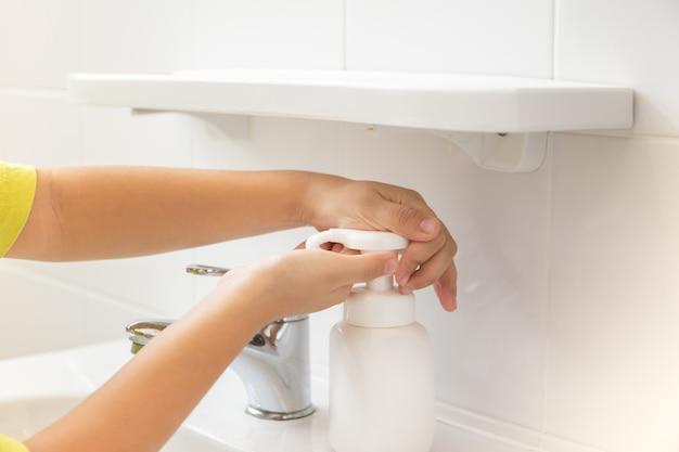 Crianças colocando sabão de espuma na mão aqui.