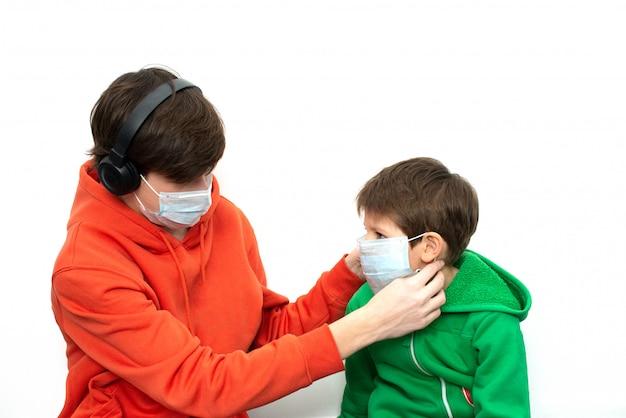 Crianças colocando uma máscara médica em roupas brilhantes. proteção contra coronavírus