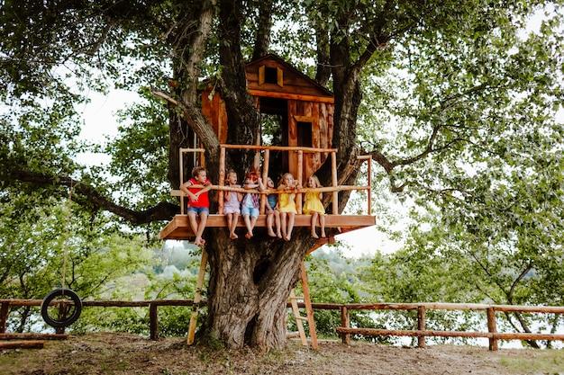 Crianças coloridas, sentado em uma casa na árvore