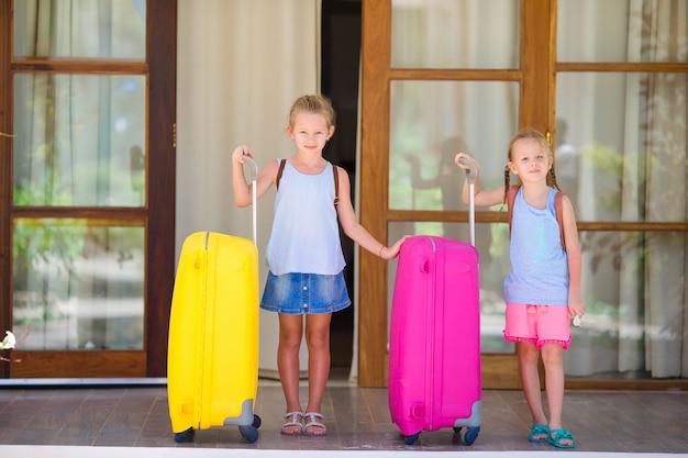 Crianças com 2 malas prontas para viajar