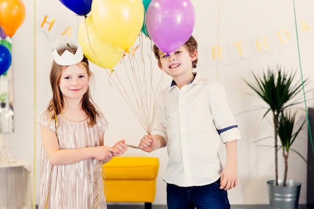 Crianças, com, balões, olhando câmera