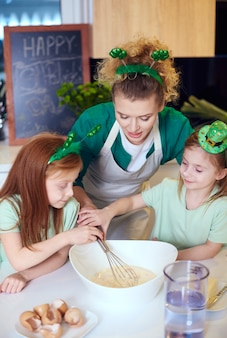 Crianças com batedor de arame assando cupcakes na cozinha