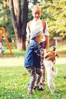 Crianças com cachorro andando no parque. família, amizade, animais e estilo de vida. crianças com cachorro jack russel terrier ao ar livre. garotos felizes brincando com o cachorro na grama verde.