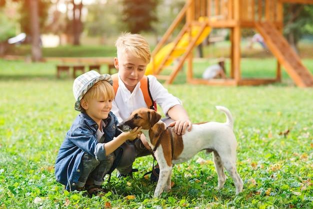 Crianças com cachorro andando no parque.