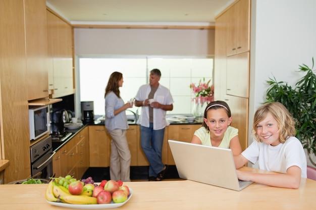 Crianças com caderno na cozinha e pais por trás deles