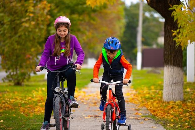 Crianças com capacetes andam de bicicleta no parque. recreação ao ar livre. parque do outono. foto com espaço vazio.