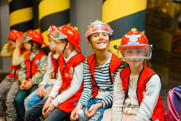 Crianças com capacetes e uniforme brincando de bombeiro