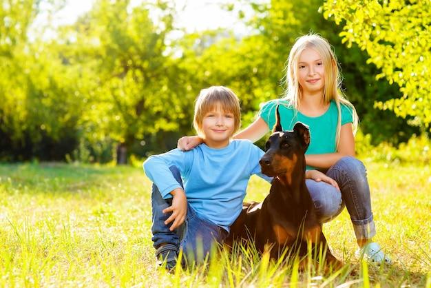 Crianças com dobermann no parque de verão.