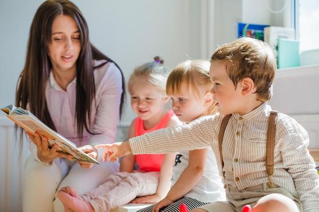 Crianças com enfermeira na sala de jogos