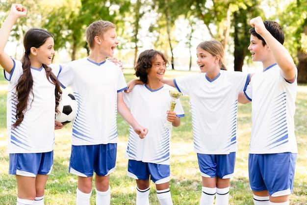 Crianças com equipamento de futebol se preparando para uma partida ao ar livre