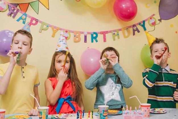 Crianças com fabricantes de ruído no aniversário de aniversário