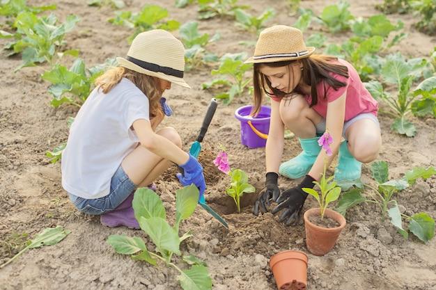 Crianças com flores em vasos, luvas com ferramentas de jardim