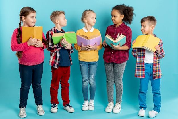 Crianças com livros olhando uns aos outros