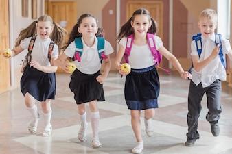 Crianças, com, maçãs, executando, ligado, corredor escola