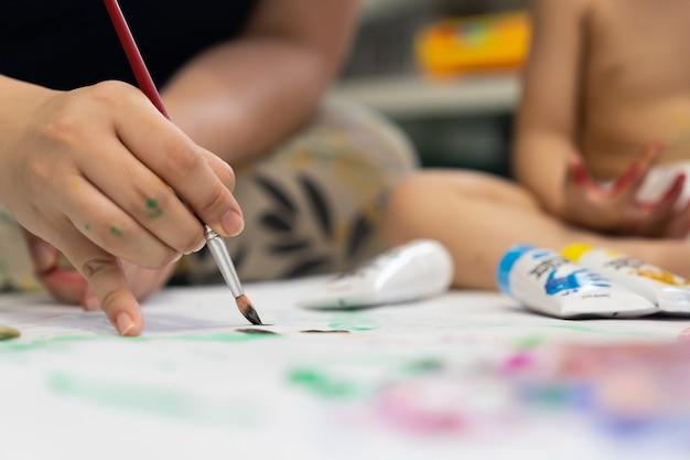 Crianças com mãe pintando imagens com aquarela pelo pincel