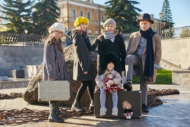 Crianças com malas de viagem, roupas retrô primavera outono. uma criança pequena sentada em uma mala