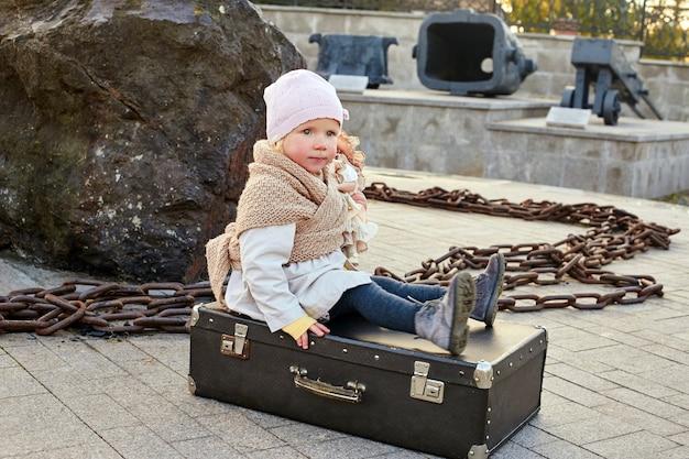 Crianças com malas viajam, roupas retrô de outono primavera. uma criança pequena sentada em uma mala e esperando o ônibus do trem. rússia, sverdlovsk, 29 de setembro de 2018